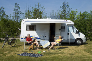 an elderly couple sitting in front of a camper
